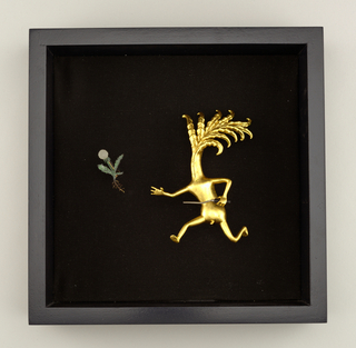Brooch composed of two components: gold leaf-covered carved maple form of human-like figure with leafy head, in a running stance and holding weeding fork (a); the other, a dandelion (b).  Stand (c) in the form of a shadow box frame; brooch parts a and b hang on metal posts positioned so that the figure appears to be chasing the dandelion.
