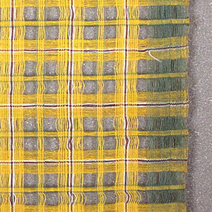 Woven plaid, predominately yellow with green, white, and purple. Spaces were left between groups of warps and wefts to form voids.  A green band is woven at the outer edges, but not where the two lengths are joined.
