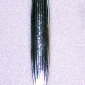 Four-tined, tapering to fluted join; plain rectangular shank ending in a rectangular platform. Handle stems from this platform in fluted, oval, organic form ending in point.