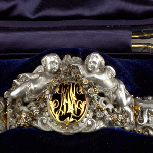 Cuff-type bracelet of five hinged, aluminum sections embellished with brass and gold; the large central section showing two winged cherubs amidst ribbons, garlands and scrollwork, floating above an oval cartouche containing an open-work gold panel with the scrolling, intertwined initials 'MJ' or 'MJC'; the central section flanked by smaller sections of strapwork and scrolls, the section on the left showing a bird and snake, the one on the right with a lizard and snake; the two outer sections of strapwork and scrolls, with attached catch and housing; the hinges, catch and housing of gold.