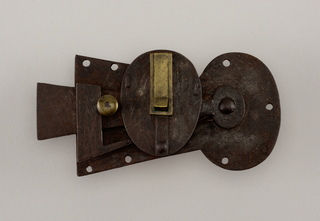 Keyhole plate latch with central oval and seven holes for screw attachment.