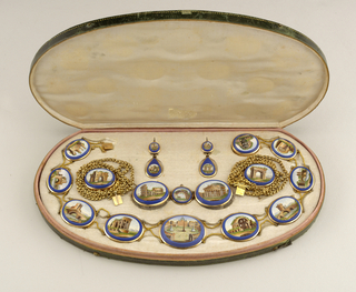 A gold oval brooch outlined in blue with an inner image of the Colisseum in Rome. Brooch is part of a set.
