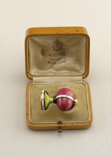 Composed of a melon shaped rhodonite held by a white enamel strap and set with a pearl on top. Mounted on a round base with a green enamel top, white enamel belt and gold base engraved with an order.