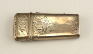 "Narrow oval in section, with hinged top and push-button closing.  Engraved cartouches formed by C-scrolls, one containing the monogram ""AB."" Inside fitted for four lancets."