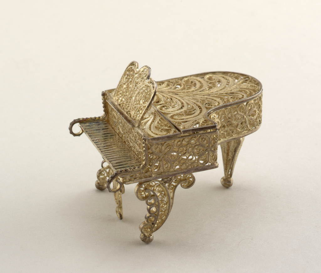 Grand piano. Lid can be raised. Scrolled front legs, baluster rear leg. All-over decoration on case and rack of scrolled and rosetted filigree.