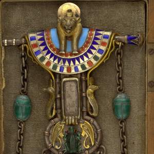 Comprising four elaborate white and gilded metal elements in the Egyptian style, three elements being a circular coin purse and two storage compartments depending from the central element composed of a mask and pectoral above a lozenge-shaped medallion and oval medallion with a green enameled frog; the whole decorated with polychrome enamel.  Large hinged clip on back of central element.