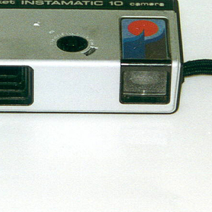 "Rectangular metal and plastic camera with black wrist strap. Imprinted at top: ""KODAK pocket INSTAMATIC 10 camera"" (a) with black button, flash cube socket on top; Kodak logo, lense and view finder on front. Separate black plastic flash cube extension (b)."