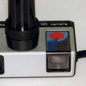 """Rectangular metal and plastic camera with black wrist strap. Imprinted at top: """"KODAK pocket INSTAMATIC 10 camera"""" (a) with black button, flash cube socket on top; Kodak logo, lense and view finder on front. Separate black plastic flash cube extension (b)."""