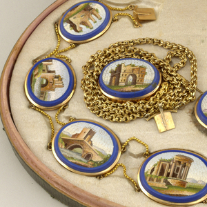 A pair of gold earrings with a teardrop connected to one oval. Oval and teardrop shapes are outlined in blue with an inner image of Italian architecture. Earrings are part of a set.