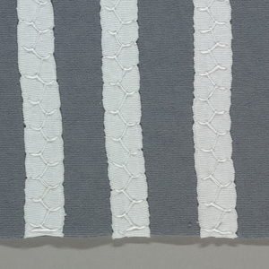 Sample of blue-gray jersey appliquéd with stripes of white jersey. Stripes are secured to the foundation using honeycomb stitch.