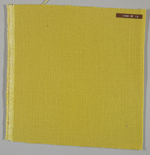 Plain weave with dark yellow warp and weft. Heavy nylon yarns give a coarse surface texture.