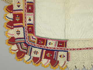 Square of undyed cotton cloth has a deep border of flat and raised crochet in white and brightly colored cottons. Border has rows of square compartments, some with diamond shapes of raised bumps, others with raised multi-petaled rosettes with glass beads in ceter and deep crocheted lobes. Narrow red and white floral tape insert forms an inner border.