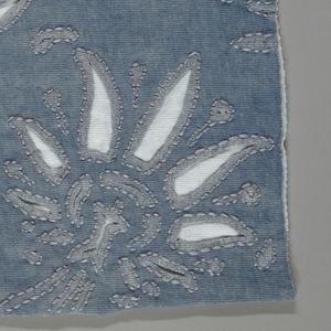Sample of blue jersey with reverse appliqué of white jersey in a floral design. Cut areas have printed outlines in a silver metallic color. Running stitch in light purple thread follows the printed outlines.