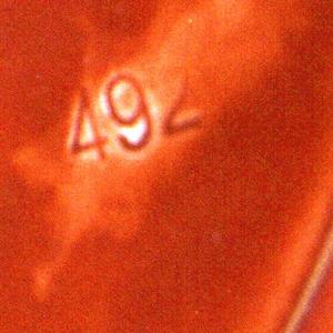 Wide shallow dish on a round foot. Orange brown glaze with cream rim.
