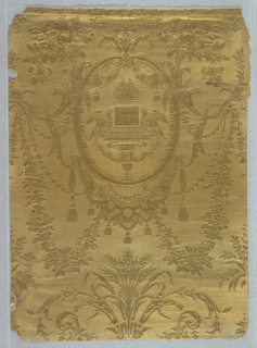Complete width. Ground ribbed horizontally, design raised with vertical cross-hatchings. Design contains numerous neo-classical motifs including an oval medallion containing draped fabric with tassels, a bracket supports two doves facing a pedestal or altar with flames. Draped fabric or lambrequin with tassels suspended from medallion. Motifs of acanthus foliage sprouting what appears to be wheat. Pomegranates appear in foliage above medallion. Printed in solid metallic gold on stamped paper.