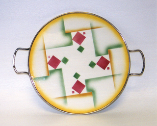 Flat circular plate with abstract atomized decoration in pink, green and yellow, showing diamonds and geometric forms. Simple rim and handles.