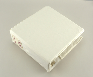 Cover for a three-ring binder made from white jersey with an appliquéd printed label on the spine area.
