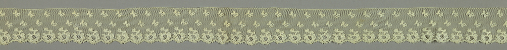 Bobbin lace border, blossom repeat; early 19th century Maline.