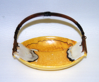 Boat-shaped dish on rectangular foot. Yellow glaze with cream and brown variations. Short protruding handles, each pierced with two holes connecting to rattan handle.