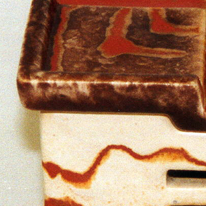 White and brick-colored earthenware box with four square feet, checkered top with opening at center (for flame) and vents on sides.