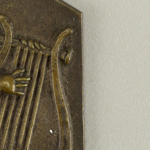 Square with upper corners clipped. Repoussé figure of seated putto playing a lyre.