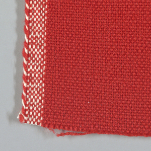 Plain weave with red-orange warp and weft. Heavy nylon yarns give a coarse surface texture.