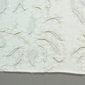 Sample of white-on-white reverse appliqué in a stylized leaf pattern.