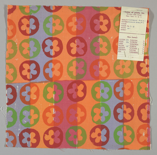 White plain weave hand printed with horizontal bands of light blue, dark pink, orange and pale orange overprinted with a flower pattern in dark red, orange and green. Color no. 7b