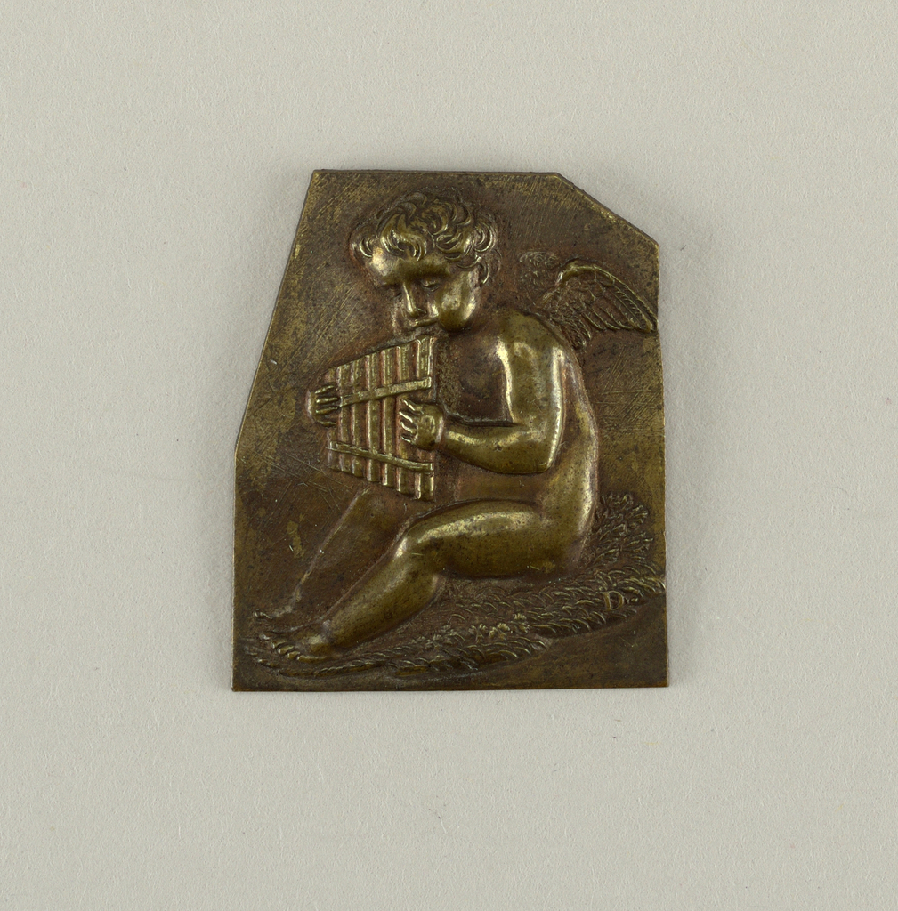 Vertical rectangle with upper corners clipped. Repoussé figure of seated putto, turned to left, paying a set of pan-pipes.