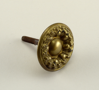 Repousee head with boss surrounded by gadrooning and band of oak leaves. Threaded bolt on back.