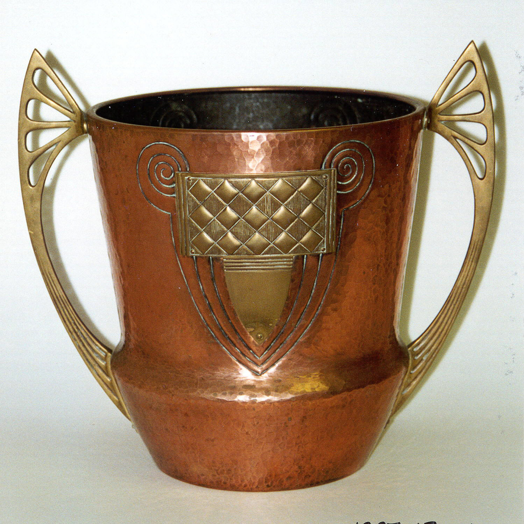 Large, tall circular cooler wider at the bottom.  Two bracing wing-like handles with cut-out shapes at top and impressed lines near the bottom.  Copper hand-hammered polished surface.  Two abstract brass appliquees surrounded by swirling and curving engraved lines sit across from each other between the handles.