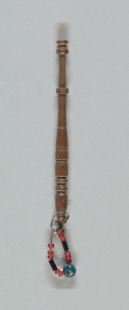 Of walnut and other wood, turned in a variety of patterns characteristic of the Midlands and Devonshire and weighted with jingled glass beads, buttons, and shells.