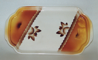 Rectangular dish on a raised bottom rim with tabs protruding from the three-lobed ends and ridged raised sides.  Diagonal patterning with central cream area containing brown airbrushed stylized flowers coming off bracing scalloped brown lines.  The two opposite corners of the dish contain airbrushed peach and yellow with a small brown squiggle on each side.