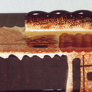 """Rectangluar dish with raised bottom rim and rectangular box set into the dish to hold butter.  Two small """"handles"""" curve off the shorter sides.  Edge of dish airbrushed brown.  Cover divided into quarters by alternating bands of handpainted and airbrushed rust and brown.  Long rectangular finial in center of the scallop-edged top.  Six sets of interlacing brown X's and brown lines and crosses as decoration."""
