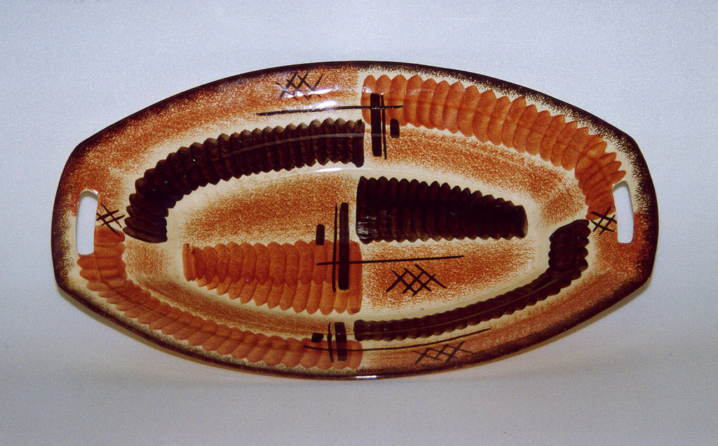 Oval concave dish with rectangular cut-out finger-holds at either end.  Cream background with surface patterning of alternating bands of airbrushed and handpainted rust and brown, virtually dividing the surface into quarters.  Airbrushed brown lines the top edge.  On surface are five groupings of brown interlaces X's and three brown crosses.