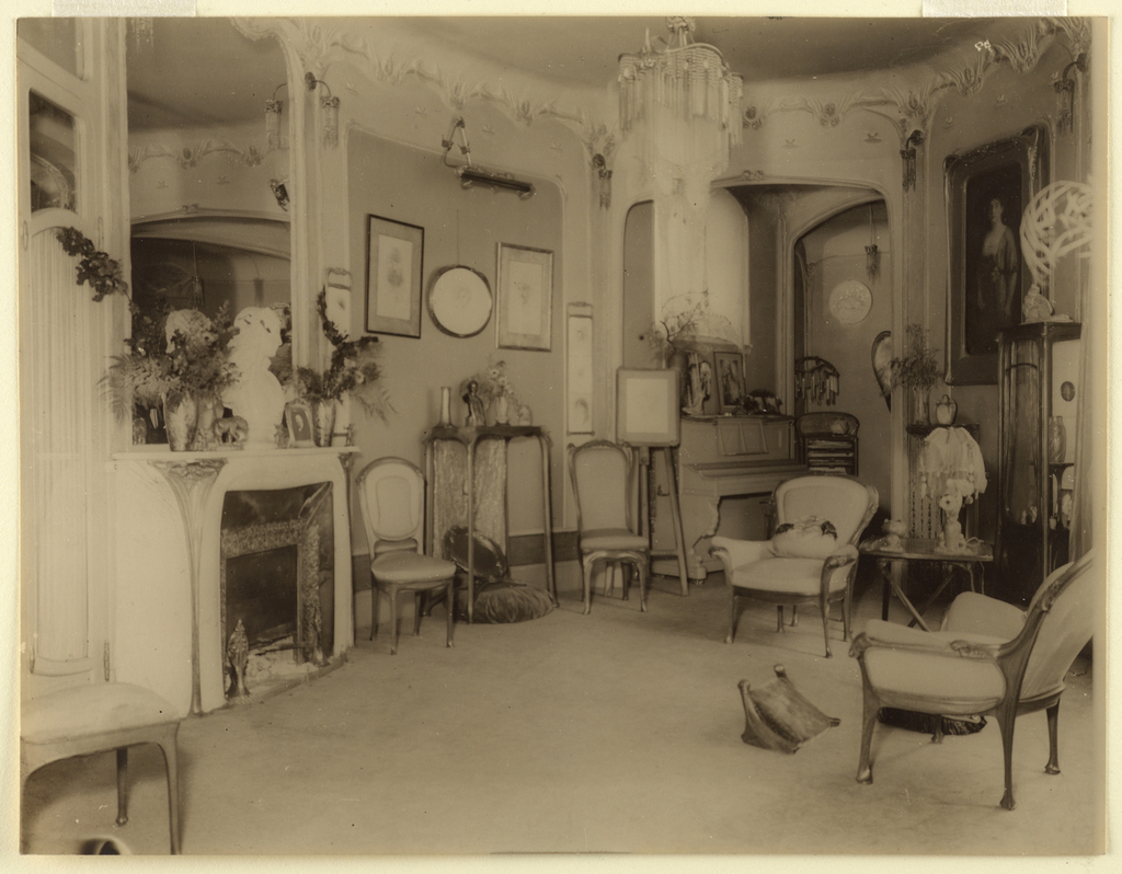 Interior view of salon of Hector Guimard's home at 22 rue Mozart. View shows sitting chairs, a fireplace with a mirror hanging above, and various pictures hanging on the wall.