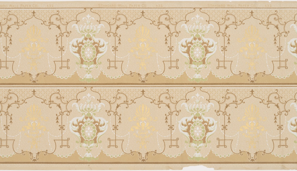 Foliate scroll medallion alternating with metallic gold anthemia medallion. Scalloped band along bottom edge. Printed in green, brown, white and metallic gold on tan ground.