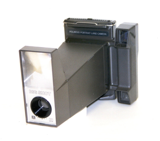 """Dark gray rectangular camera with handle, and flash with words """"BIG SHOT""""."""