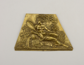 Irregular polygon with repoussé figure of a woman reclining on rocks, holding a mirror in her right hand and a cornucopia in the left. Allegorical figure of autumn.
