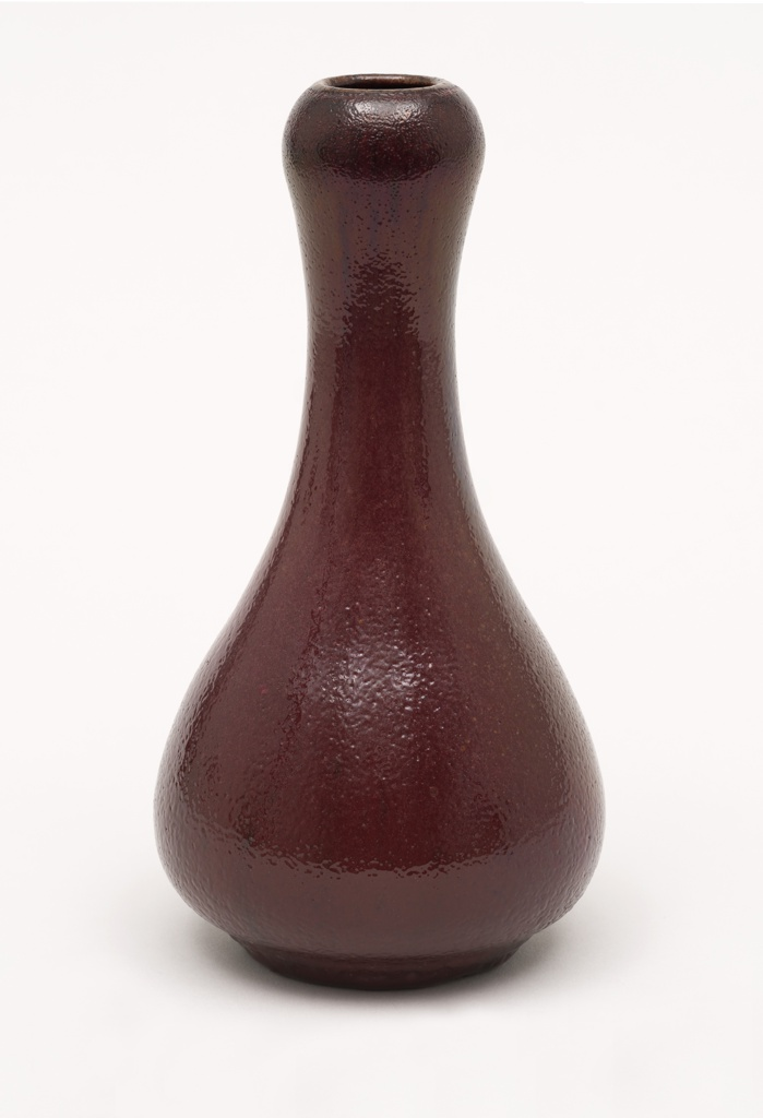 Gray-white stoneware body, thrown. Bulbous body with tapering neck; with slightly bulging area below rim; flat foot. Covered with a deep red or scarlet glaze with slight golden luster effect. Black striations through glaze. Very dark red at rim bulge. Dimpled surface allover. Interior glazed. Bottom not glazed. Glaze very thick at base.
