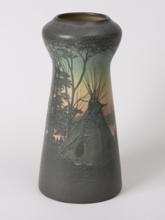 White clay body, thrown.  Cylindrical body, tapering upward, waisted below bulbous shoulder, truncated neck; no foot.  Decorated in silhouette around body with scene of Indian encampment along river bank.  Design of two teepees among trees in foreground with figures of Indians doing various activities--gathering wood and twigs, cooking, etc.  Across river more teepees.  Bottom third of body mottled dark green and brown.  Lower sky and river subtly shaded orange into pale yellow, upper sky shading into blue-green.  Figures, teepees and foliage in shades of brown and dark green.  Interior, white, glazed; bottom glazed.  Allover vellum glaze, cracklature.