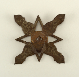 Square mount, pierced and shaped to eight part design of projecting barbs and petals. Nail with square molded head on a square shank.