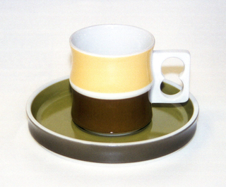 Cup (a): cylindrical white body formed of two concave sections, one above the other, white pierced rectangular handle on side; exterior of top section glazed in yellow, bottom section in dark green. Saucer (b): circular form with slightly concave upright rim; white body glazed green on interior, dark green on exterior rim.