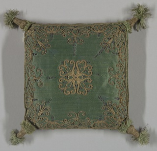 Small cushion of dark green satin embroidered in gold cord. Corners have tassels.