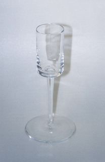 Clear transparent cylindrical cup on slightly tapering attenuated stem with broad flat circular foot.