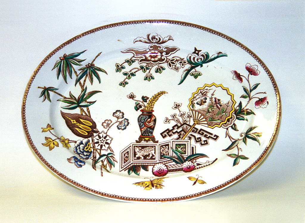 Oval form, the white ground  transfer-printed with Chinese- or Japanese-inspired polychrome decoration including plants, butterflies, fan, vase of flowers, screen, and geometric patterns. The rim with tan band and brown decoration.