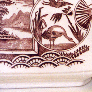 Roughly rectangular hexagonal body with rectangular mouth, raised curved spout and shaped handle; white ground with brown Japanese-inspired transfer-printed decoration of framed landscape and fan showing cranes(?) among water plants, superimposed on flowering branches above a geometric pattern.  Flowering branch decoration along rim of mouth and geometric pattern along back of  handle.