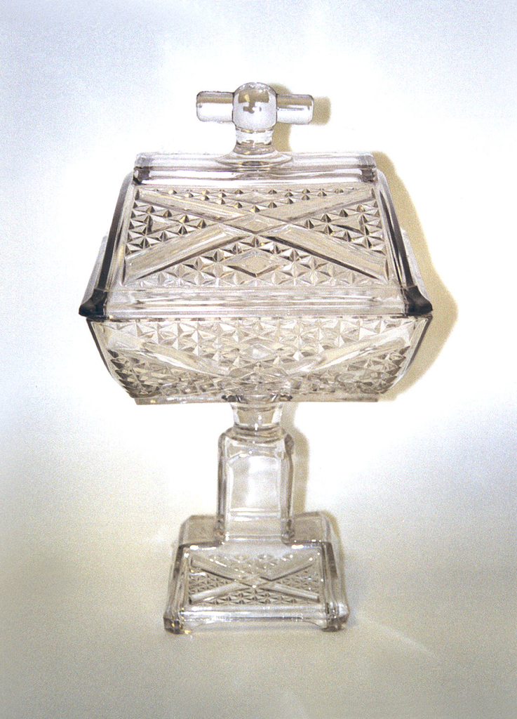 Of thick clear glass.  The roughly rectangular curving bowl (a) molded with wide bands forming an x within diamond-patterned triangular quadrants above a squared shaft on a spreading rectangular foot, the front and back panels repeating the pattern in the bowl. The roughly rectangular curving lid (b) also repeating the band and diamond pattern, and having a T-shaped handle.