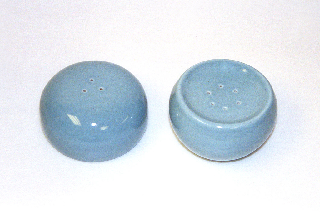 "Circular shaker (a)  tapering to base, slightly depressed circular top pierced with six holes; cork stopper (b) in bottom; ""ice blue"" glaze."