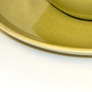 """Hemispherical cup (a) with thick circular loop handle; """"avocado"""" yellow-green glaze.  Circular saucer (b) with raised edge as rim; """"avocado"""" yellow-green glaze."""